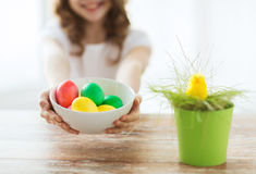 Close up of girl holding bowl with colored eggs Stock Image