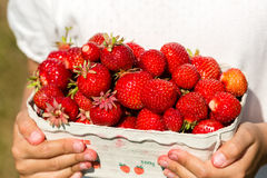 Close-up of girl holding box of strawberries Stock Photo
