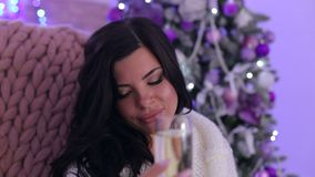 Closeup of girl with champagne near Christmas tree stock video