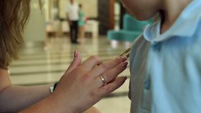 Close-up of a girl holding a phone in the hotel, and child looks into the screen. Close-up of a girl holding a phone sitting in the lobby of a hotel or cafe, a stock footage