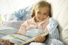 Close-up of a girl holding a picture book on the bed. Stock Image
