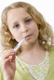 Close up of girl holding thermometer in mouth Royalty Free Stock Image