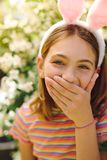 Close up of a girl laughing. Portrait of a girl wearing rabbit ear headband laughing covering her mouth. Cheerful girl laughing with her hand on her mouth stock image