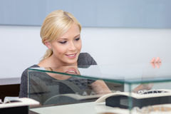 Close up of girl looking at jewelry in glass case Royalty Free Stock Photo