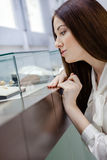 Close up of girl looking at jewelry in window case Stock Photo