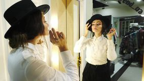 Close-up girl looking in the mirror and try on a black hat. stock video
