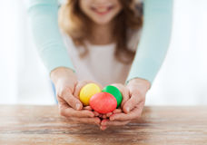 close up of girl and mother holding colored eggs Stock Photo
