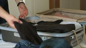 Close-up of the girl packing a suitcase on the bed in the bedroom. Woman preparing luggage to go on vacations. Tourist are packing luggage for travel. Slow stock video footage