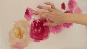 Close-up girl draws a finger on the canvas. Art. Close-up girl paints peonies with her finger on the canvas. The artist paints pink flowers on canvas with her stock footage