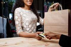 Close up of girl paying for buyings in shopping mall. Close up photo of young beautiful african girl paying for buyings, smiling in shopping mall stock images