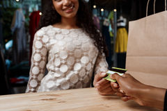 Close up of girl paying for buyings in shopping mall. Close up photo of young beautiful african girl paying for buyings, smiling in shopping mall stock photography
