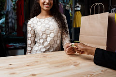 Close up of girl paying for buyings in shopping mall. Close up photo of young beautiful african girl paying for buyings, smiling in shopping mall royalty free stock photos