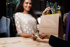 Close up of girl paying for buyings in shopping mall. Close up photo of young beautiful african girl paying for buyings, smiling in shopping mall stock photo