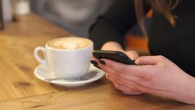 Close-up of girl with a phone in her hands in a coffee shop sitting at the table stock footage
