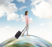 Close up of girl in pink shirt walking on the globe with sky. Close up portrait of woman in pink shirt with black suitcase walking on huge globe. Concept of Stock Images