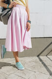 Close-up of girl in pink skirt, yellow shirt and with a backpack Royalty Free Stock Photo