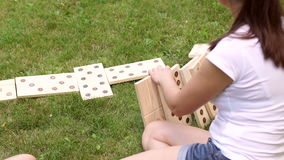 Closeup of girl playing in giant dominoes on grass stock video footage