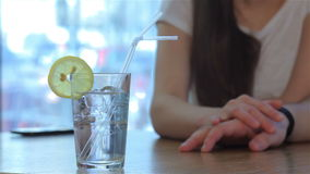 Close up of girl puts her hand on the man's hand. Close up girl putting her nice hand on man's hand. Close up of transparent glass of cocktail with a straw and stock video footage