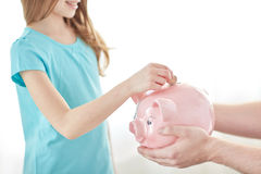 Close up of girl putting coin into piggy bank Royalty Free Stock Photos