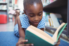 Close up of girl reading book in library Stock Photo
