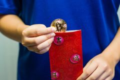 Girl opening Red Packet. A close up of a girl removing a Bitcoin coin from a traditional red packet stock photos
