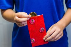 Girl opening Red Packet. A close up of a girl removing an Etherium coin from a traditional red packet Stock Image