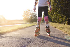 Close up of girl rollerblading in park. Outdoor, recreation, lifestyle, rollerblading. Close up of girl rollerblading in park at sunset. Outdoor, recreation Royalty Free Stock Images