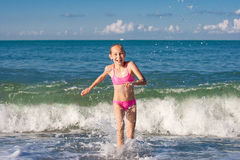 Close-up girl running from sea wave or surf Royalty Free Stock Photo