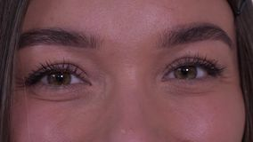 Close-up of the girl`s eyes looking sideways, then into the frame and smiling. 4K Slow Mo. Close-up of the girl`s eyes looking sideways, then into the frame and stock video