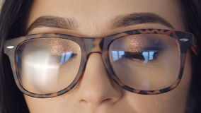 Close up of girl`s eyes opening and looking to camera in glasses. Full HD stock video