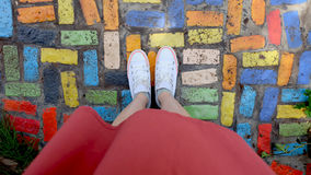 Close Up on Girl`s Feet Wearing White Sneakers Standing on Coloful Tile. Great For Any Use Royalty Free Stock Photo