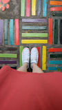 Close Up on Girl`s Feet Wearing White Sneakers Standing on Coloful Tile. Great For Any Use Stock Image