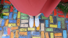 Close Up on Girl`s Feet Wearing White Sneakers Standing on Coloful Tile. Great For Any Use Stock Photography