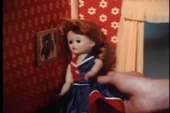 Close-up of girl's hand playing with doll in dollhouse stock video footage