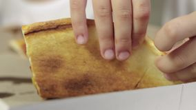 Close-up of the girl`s hand takes a piece of juicy, greasy pizza and brings it into her mouth. Unhealthy food concept. 4k resolution stock video