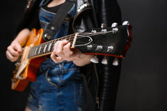 Close up of girl's hands on guitar over black background. Stock Image