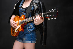 Close up of girl's hands on guitar over black background. Close up of girl's hands on guitar over black background in jeans royalty free stock image