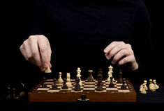 Close-up of the man's hands, which transposes a pawn on a woode Stock Photo