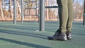 Close-up of girl`s legs in an open area for workout at the horizontal bar.  stock video