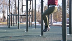 Close-up of girl`s legs on the open area for workout. Woman shakes the press hanging on the horizontal bar.  stock footage