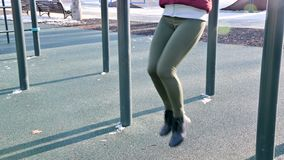 Close-up of girl`s legs on the open area for workout. Woman shakes the press hanging on the horizontal bar.  stock video