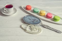 Close up. Girl`s morning. Bright colorful macarons, a cup of berry tea, a pocket mirror, a pearl thread. White background royalty free stock photo