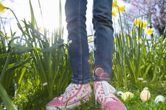 Close up of girl's sneakers and decorated Easter eggs Stock Photography