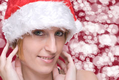 Close up girl in santa hat over light bokeh Royalty Free Stock Photography
