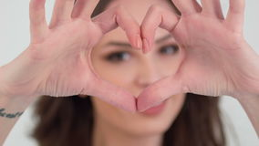 Close-up of girl showing heart with fingers stock footage