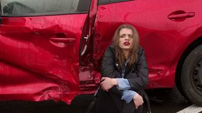 Close-up of girl sitting on the ground near a broken car, she was in an accident. Close-up of a girl crying sitting on the ground near a broken car, she was in stock footage