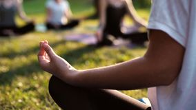 Close-up of girl sitting in lotus position and meditates morning in park stock video footage