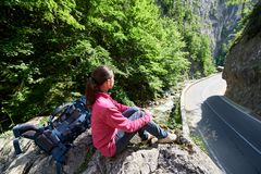 Close-up girl sitting on stone enjoying scenic terrain Bicaz Canyon. Close-up of a girl sitting on a stone beside a backpack under the sunbeams enjoying the Royalty Free Stock Photography