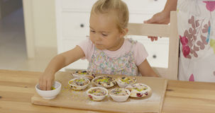 Close up on girl sprinkling toppings  muffins Royalty Free Stock Image