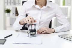 Close up of a girl stamping a document. Close up of a woman in white blouse who is sitting in the office and stamping a document. Concept of notary work royalty free stock image